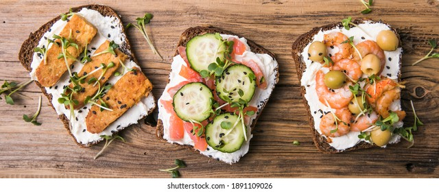 Variety of sandwiches for breakfast, snack, appetizers - tempeh, salmon, prawns grilled whole grain bread sandwiches with microgreens. on a wooden background