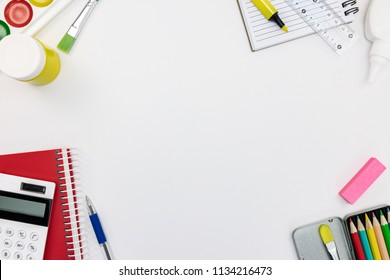 variety of school supplies and tools on white desk background. school stationary flat view