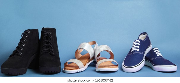 Variety of seasonal shoes. Sandals, boots, sneakers on blue background.