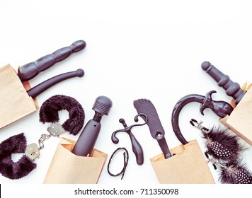 A variety of sex toys (dildo, vibrator, handcuffs, anal plug and others) are in paper bags. Image for sex shop advertising, promotion on the Internet, discounts and sales, email newsletters and other