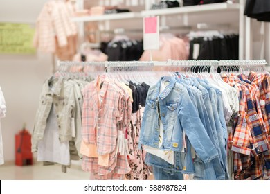 Variety of short sleeve shirts and jeans jackets on hangers in kids clothes store