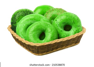 A variety of six green bagels in a basket, isolated against a white background