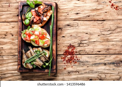 Variety of small sandwiches.Bruschetta on wooden cutting board.Bruschetta is traditional Italian common folk dish.