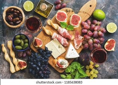 A variety of snacks, prosciutto,grapes, wine, cheese with mold, figs, olives on a rustic background. Top view,flat lay