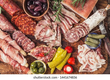 Variety of Spanish appetizer on wooden board, wine snack set, salami, ham, olives, sausages, bacon, bread sticks other appetizer and wine, Spanish tapas.