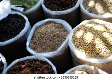 Variety of spices in the Asian market. Grains of different spices in large bags close-up. Zira, coriander, cloves, star anise, spices in the eastern bazaar.