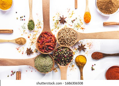 Variety of spices and herbs in spoons and bowls on white background. Top view. Cooking ingredients and condiments concept.