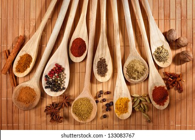 Variety of spices on wooden spoons and bamboo mat