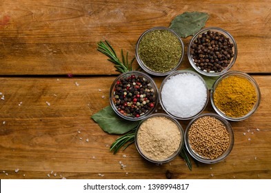 Variety of spices in round glass bowls - ground ginger, hops-suneli, kari, black pepper and mix on a wooden table