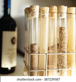 Variety of spices in test tube with bottle or red wine in the background