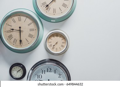 Variety style of vintage clocks hanging at the wall.  Wall clock isolated on the white background. Five wall clocks showing time in different capitals of the world. World time interior concept.