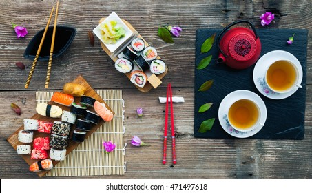 A variety of sushi and green tea set on rustic wooden table. Sushi rolls, nigiri, raw salmon steak, rice, cream cheese, avocado, lime, pickled ginger.