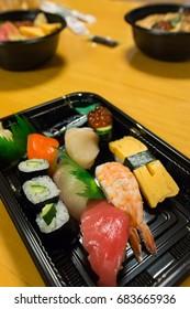 variety of sushi on the black plate, tuna, salmon, shrimp and tamagoyaki