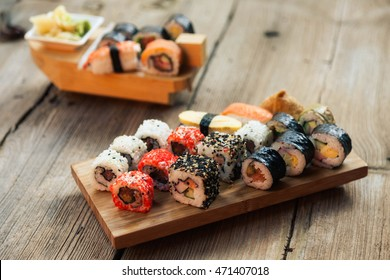 A variety of sushi on old wooden table. Sushi rolls, nigiri, raw salmon steak, rice, cream cheese, avocado, lime, pickled ginger.