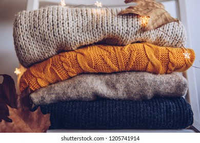 Variety of sweaters piled up on chair