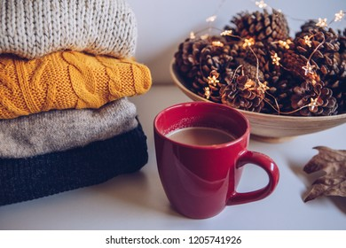 Variety of sweaters piled up on table in autumn arrangement
