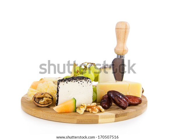 Variety of swiss cheese on a plate with walnut, grapes and dates