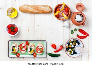 Variety of Tapas and Pintxos Snacks on light wood table shot from above as a border with copy space in the center