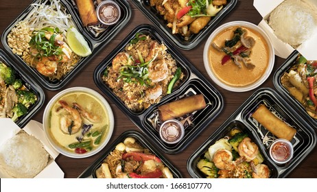 Variety of Thai food on wooden table. To go / delivery box.