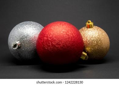 Variety of three Christmas tree decorations on a dark background