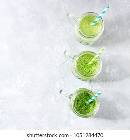 Variety of three color green spinach kale apple yogurt smoothie in mason jars in row with retro cocktail tubes over gray background. Healthy vegan detox eating. Top view, copy space. Square image