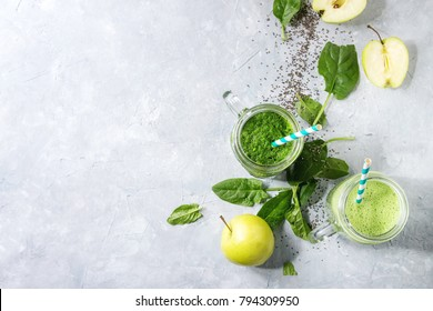 Variety of three color green spinach kale apple yogurt smoothie in mason jars with retro cocktail tubes and ingredients above over gray texture background. Healthy vegan detox eating. Top view, space