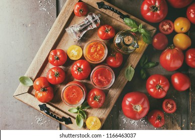 Variety of three homemade tomato sauces in glass jars with ingredients above. Different kinds of tomatoes, basil, olive oil, pepper, salt in wood tray over old grey wooden background. Flat lay, space