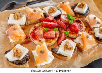 Variety of toasted sourdough bread with: smoked salmon fillet and cream cheese; marinated eggplant with walnuts and grilled goat cheese with strawberr