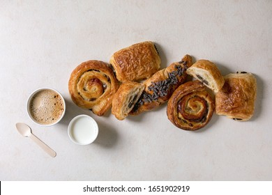 Variety of traditional french puff pastry buns with rasin and chocolate, croissant with paper cup of coffee and milk, recycled wooden spoon over white texture background. Flat lay, space