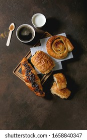 Variety of traditional french puff pastry buns with rasin and chocolate, croissant with paper cup of coffee and milk, recycled wooden spoon of cane sugar over dark texture background. Flat lay, space