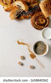 Variety of traditional french puff pastry buns with rasin and chocolate, croissant with paper cup of coffee and milk, recycled wooden spoon of cane sugar over white texture background. Flat lay, space