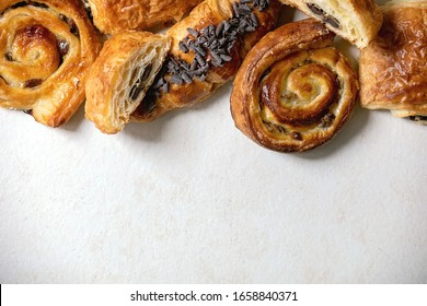 Variety of traditional french puff pastry buns with rasin and chocolate, croissant over white texture background. Flat lay, space