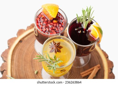 Variety of traditional winter sweet hot alcohol drinks mulled red wine  glintwine and  white rum with orange, spices, cinnamon, rosemary, anise served on wooden board