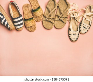 Variety of trendy woman's summer shoes. Flat-lay of espadrilles, sandals, flip flops made of natural materials over pastel pink background, top view, copy space. Summer season footwear apparel concept