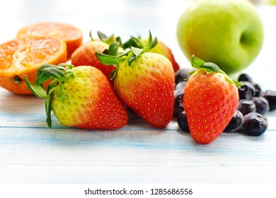 Variety of tropical fruit have high vitamin c is good for health and anti-oxidant, probiotic consist strawberry, green apple, orange, blueberry on blue isolated, natural food, organic fruit concept