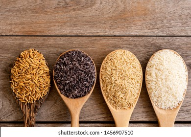 Variety type and color of rice ; paddy rice, riceberry ,brown coarse rice and white thai jasmine rice in wooden spoon  isolated on old rustic wood table background. Healthy food concept. Flat lay.