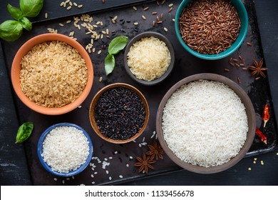 Variety of types and colours of rice - red, black, basmati, whole grain, long grain parboiled and arborio - in bowls. Overhead view