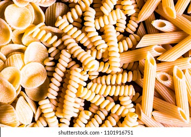 Variety of types and shapes of dry Italian pasta - fusilli, orecchiette and penne, top view. Uncooked whole wheat fusilli italian pasta background. Pasta pattern. Food background.