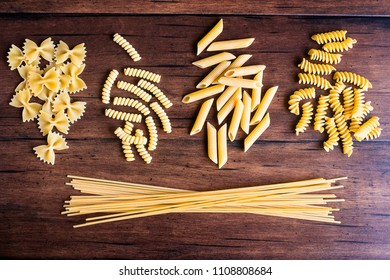 Variety of types and shapes of dry Italian pasta - fusilli, spaghetti, farfalle and penne, top view. Uncooked whole wheat italian pasta. Image with copy space.
