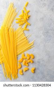 Variety of types and shapes of dry Italian pasta - Spaghetti, Linguine, Conchiglie, Elbow macaroni, Fusilli.