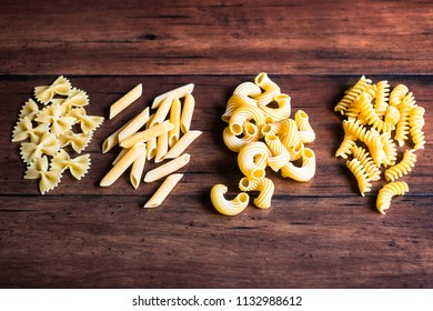 Variety of types and shapes of dry Italian pasta - fusilli, farfalle or bow tie pasta, cavatappi and penne, top view. Uncooked whole wheat italian pasta. Image with copy space.