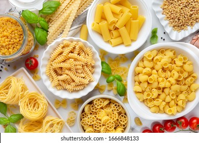 Variety of types and shapes of dry pasta - fusilli, penne, fettuccine nests, mafaldine, shells, bowtie and wheels - in white bowls with traditional Italian cuisine ingredient fresh basil and tomatoes