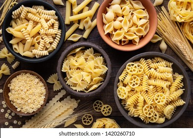 Variety of types and sshapes of dry Italian pasta in bowls against dark rustic wooden background