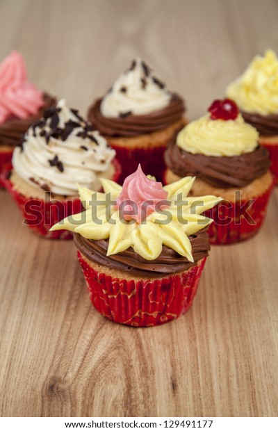 Variety of vanilla cupcakes with colorful frosting on wood