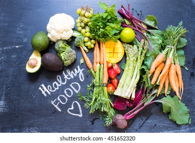 Variety of vegetables and fruits on a blackboard, top view. Vegan and healthy concept.