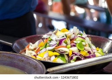 A variety of vegetables on frying pan at the Bergen fishmarket.