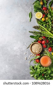Variety of vegetarian healthy eating food ingredients. Green asparagus, herbs, tomatoes, nuts, wheat corns, dandelion leaves, glass of juice over grey texture background. Top view, copy space.