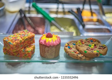 A variety of vibrantly colored treats including rice marshmallow treats, a cupcake and candy speckled cookies laid out on a platter.
