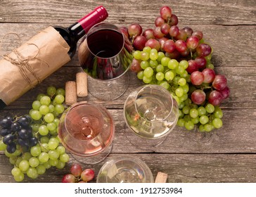 Variety of wine and snack set. Different types of grapes. Fresh ingredients on wooden background. Top view