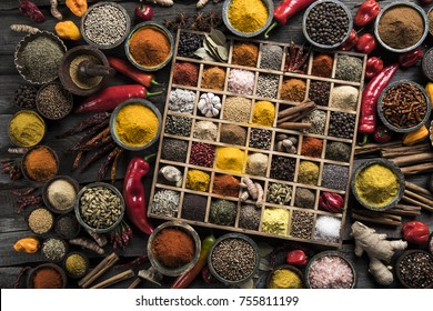 Variety of wooden box, spices and herbs on kitchen table